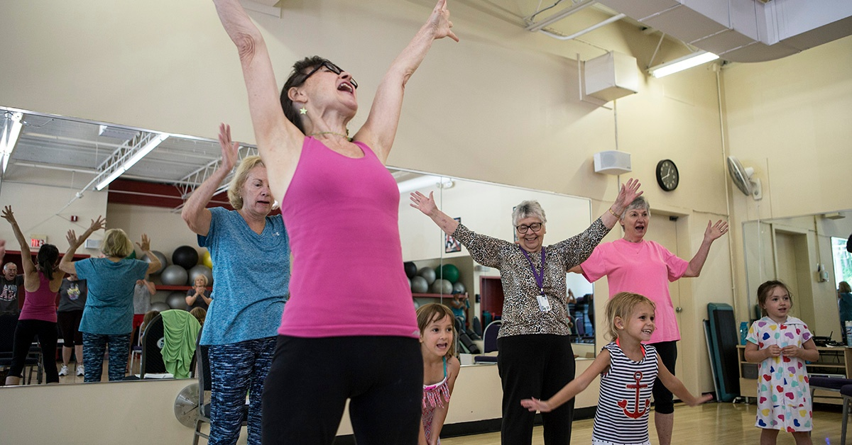 Active Seniors with kids arms in the air