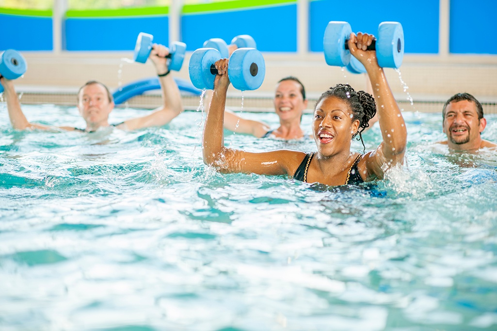 Group aqua fitness class with  weights