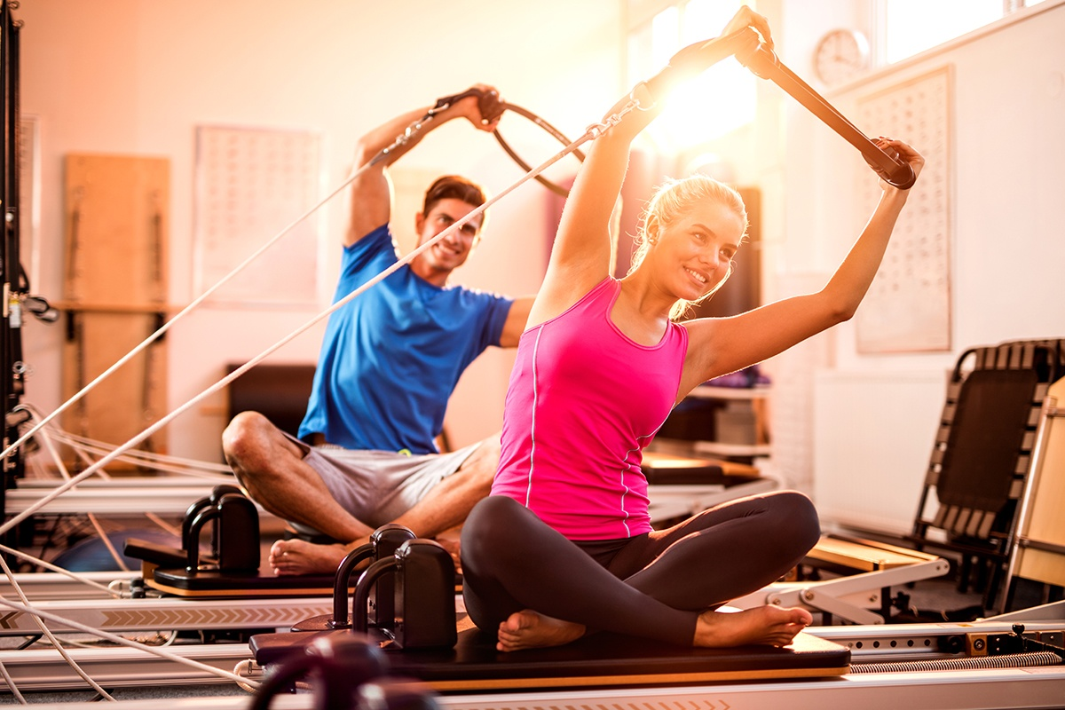 Couple stretching on pilates equipment