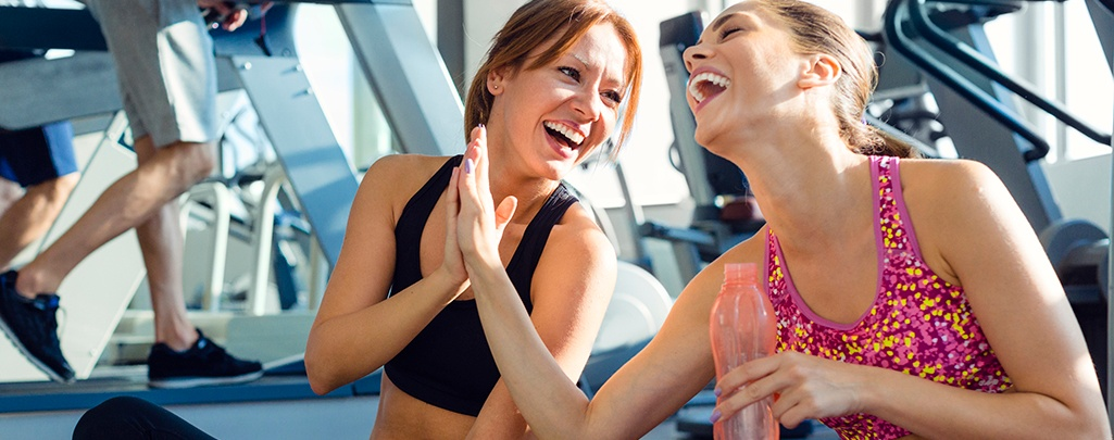 Two friends high five at gym. Keep yourself accountable by meeting a friend at the gym.