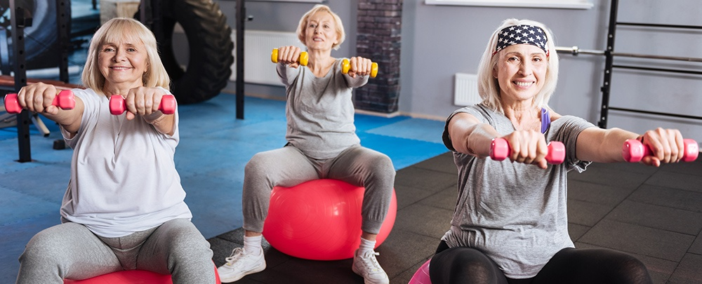 Three senior women sitting on exercise balls holding small free weights. Exercise benefits you brain.