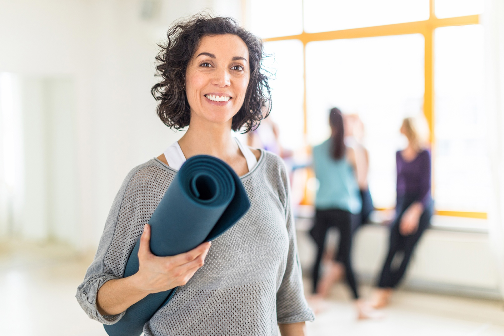 Woman with yoga mat at yoga class