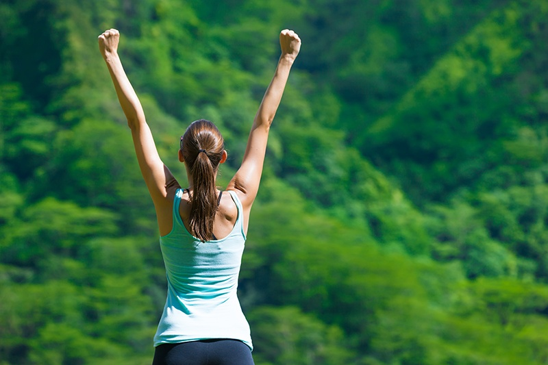 Woman feeling great arms in air outside
