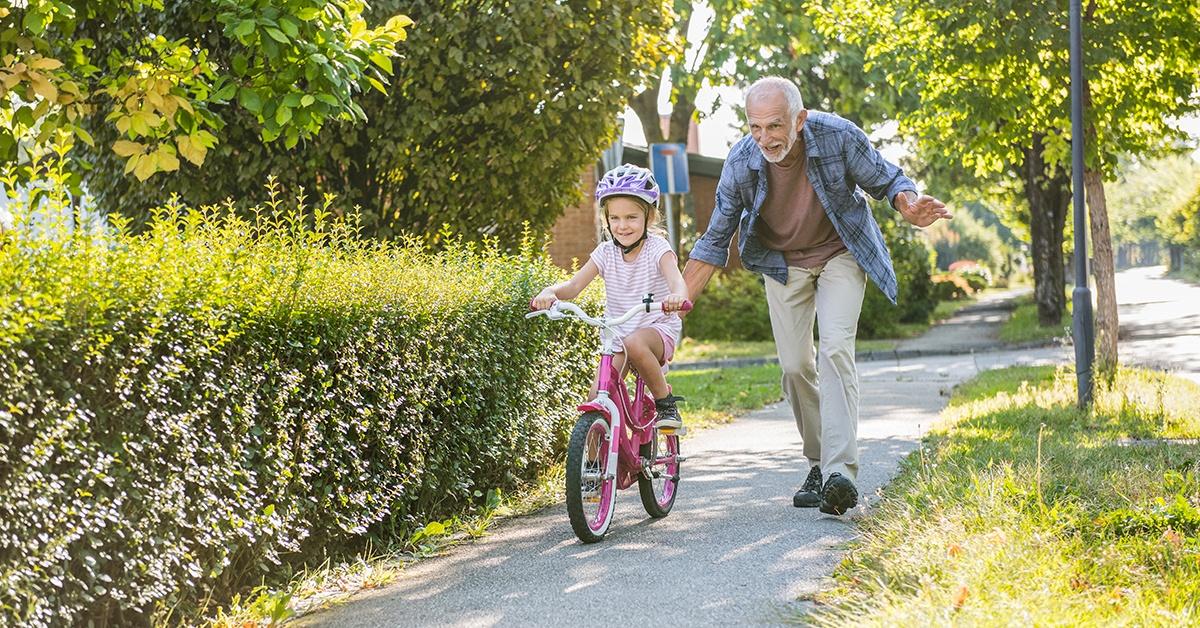 Grandpa pushing grandaughter on bike - exercising together.