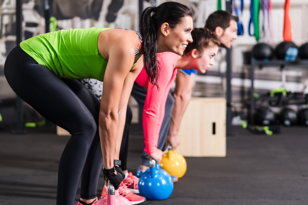 Happy people doing a kettlebell workout.
